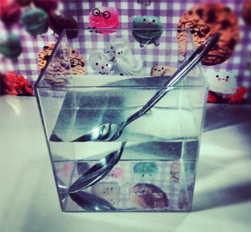 refracción: cucharilla en un vaso con donuts parlantes al fondo